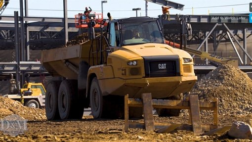Woman employee driving truck on site